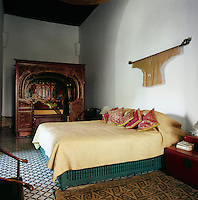 In the white bedroom, the bed is from a 'house of pleasure' in Canton, the red armoire is from Sichuan and the chairs belonged to concubines in a Peking palace. On the walls are the robes of Mandarins. The ancient floor mosaics are in black and white.