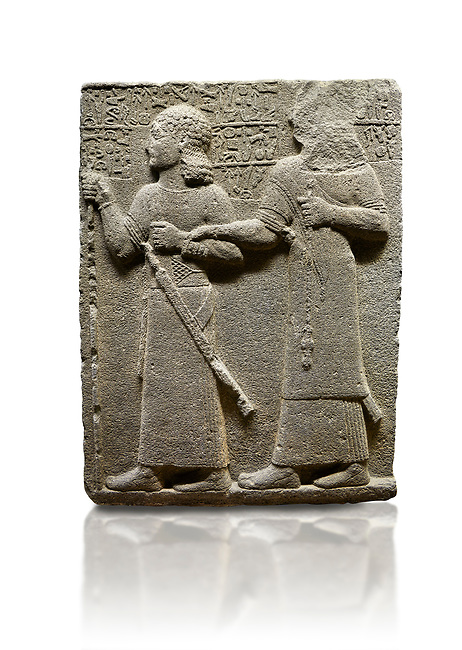 "Hittite monumental relief sculpted orthostat stone panel of Royal Buttress. Basalt, Karkamıs, (Kargamıs), Carchemish (Karkemish), 900-700 B.C. Anatolian Civilisations Museum, Ankara, Turkey.<br /> <br /> King Araras holds his son Kamanis from the wrist. King carries a sceptre in his hand and a sword at his waist while the prince leans on a stick and carries a sword on his shoulder. <br /> <br /> Hieroglyphs reads; ""This is Kamanis and his siblings. I held his hand and despite the fact that he is a child, I located him on the temple. This is Yariris' image"".  <br /> <br /> Against a white background."