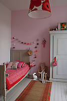 A signature wall in rose pink adds depth and contrast to this child's bedroom