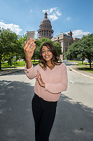 Young businesswoman taking a selfie portrait with her mobile smart phone on the Texas State Capitol grounds in downtown Austin, Texas.