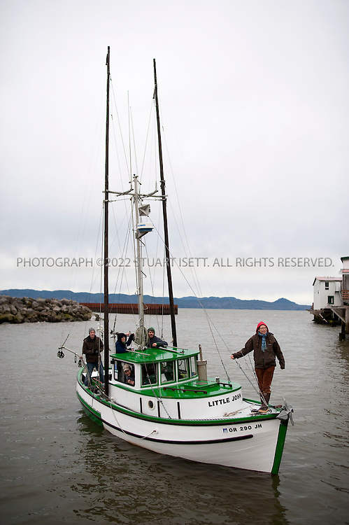 2/28/2009--Astoria, OR, USA..Moe Bowstern arrives at Pier 39 in Astoria in a restored salmon fishing boat 'Little John'. Bowstern was in Astoria to perform at the fisherman poetry festival. ..Pier 39 in Astoria, OR, on the banks of the Columbia River is a former salmon accnery converted into office space, cafes, restaurants and a museum of the salmon industry that once thrived in Astoria. It's is  the oldest waterfront building in the town...©2009 Stuart Isett. All rights reserved.