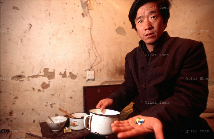 QSFeature02AIDS015 20020212 DONGGUAN, CHINA:  .AIDS patient Wang Liang takes a drawer-full of anti-biotics and cold medicine in hope of easing his chroninc headaches, fevers and diarrhea at his home in Dongguan Village, Henan Province, China 12 February 2002. Over 700,000 peasant farmers have contracted the HIV virus when they participated in the unregulated blood selling/buying boom of the early and mid nineties. .Photo by: Qilai Shen...