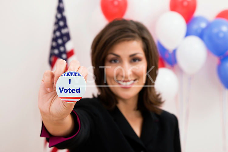 USA, Illinois, Metamora, Portrait of smiling woman holding vote button, US flag and balloons in background