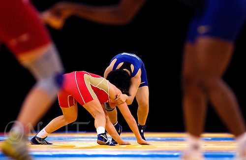 11 DEC 2011 - LONDON, GBR - Xiluozhuoma (CHN) (in blue) attempts to overpower Inna Trazhukova (RUS) (in red) during their 63kg category quarter final bout during the London International Wrestling Invitational and 2012 Olympic Games test event at the ExCel Exhibition Centre in London, Great Britain .(PHOTO (C) NIGEL FARROW)