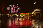 Sunrise at the Pike Place Market with neon signs illuminated in the pre dawn morning with reflections on brick road downtown Seattle, Washington State USA