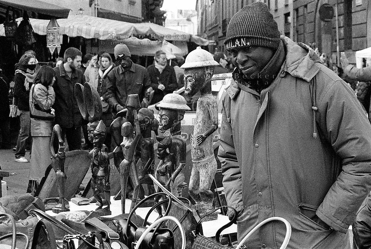 Milano, quartiere Sant'Ambrogio. Fiera degli Oh Bej! Oh Bej!, tradizionale mercatino del periodo natalizio milanese. Un ragazzo africano con un cappello dellla squadra di calcio del Milan vende borsette contraffatte --- Milan, Sant'Ambrogio district. Oh Bej! Oh Bej!, traditional Milanese Christmas fair. An African guy with a hat of AC Milan football team sells counterfeit handbags