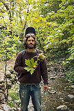 USA, Oregon, Ashland, portrait of Carston Peer in Lithia park holding flowers and leaves that he has collected and woven into a wreath