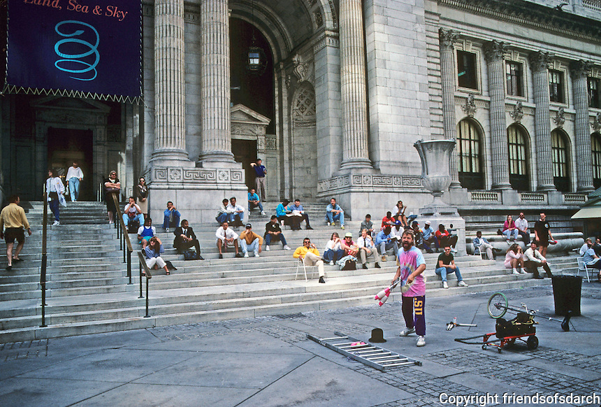 New York: New York Public Library--an entertainer on street in front of steps. Photo '91.