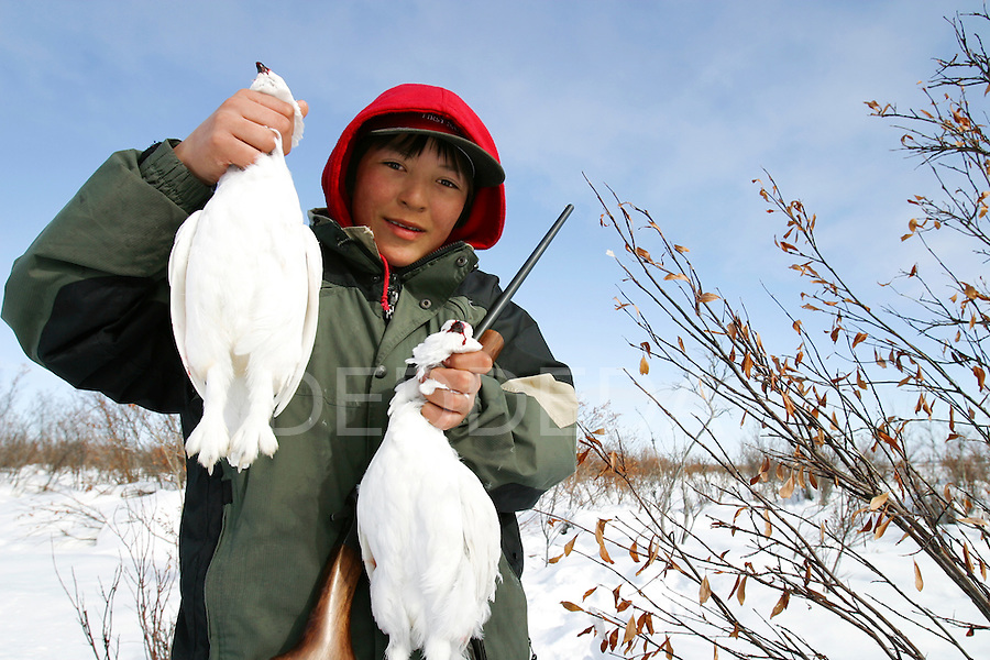 Jay Charlie, 11, a young member of the Vuntut Gwitchin First Nation, smiles as he holds his hunted ptarmigan near Old Crow, Yukon Territory, Canada.