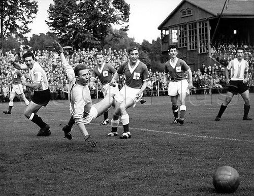 The Argentine striker Norberto Menendez (l) shoots the ball from inside the Northern-Irish box while goalkeeper  Harry Gregg attemps a save (2.v.l.). Aslo shown is captain of N-Ireland Danny Blanchflower (M, in front).  Argentina wins the game in the world championship in Sweden on 11.06.1958 before 14,200 spectators in the Trjansvall stadium in Halmstad the group game  against Northern Ireland by a score of 3:1