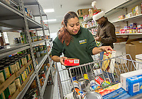 NWA Media/JASON IVESTER --12/18/2014--<br /> Iris Calderon (left) and Edward Gray sort and shelve donations in the food pantry on Thursday, Dec. 18, 2014, inside Helping Hands in Bentonville. Employees and volunteers are preparing for their annual Christmas meal distribution.