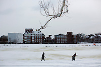 People walk along the Charles River in Cambridge, Massachusetts, USA, on Saturday, Feb. 9, 2013, after Winter Storm Nemo hit the area.