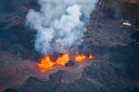 lava emanating from Pu'u O'o on Kilauea Volcano, erupts in three fountains from a fissure in Leilani Estates subdivision, near Pahoa, Puna, Big Island, Hawaii, USA, at upper right frame, the remains of a metal roofed structure are consumed by fire and an asphalt road is covered by lava