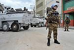 An Indian soldier, part of the United Nations Mission in Haiti (MINUSTAH), stands in a Port-au-Prince street while other soldiers secure the area behind him in a security operation following the January 12 earthquake.
