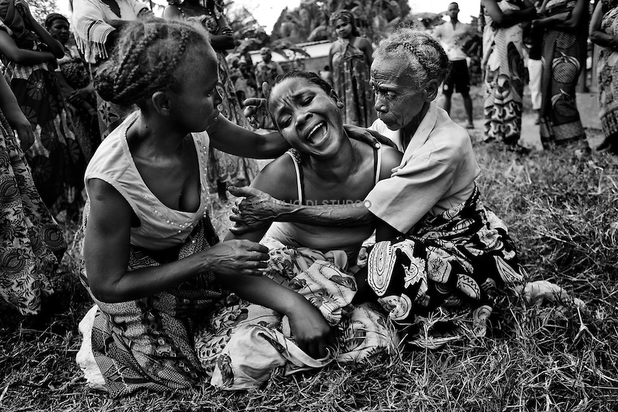 MADAGASCAR, AMBANJA, AUGUST 2013: <br />The Funeral of Dina, 08 Aug, 2013.<br />Dina, 33, was killed two days earlier by the police with a headshot. The official version of the police said that the cops had gone there to arrest him, when he realized what was happening he reacted lunging toward the cops with a machette, and the cops had to shoot to legitimize the defense.<br />The Wife version it is complitely different she said to me:<br />while we were sleeping, police broke down the door and 'entry into the house. They handcuffed my husband and asked him three times if he was Dina.<br />then they bumped near the door and fired two shots in the head. @Giulio Di Sturco