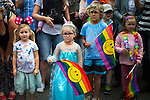 © Joel Goodman - 07973 332324 . 27/08/2016 . Manchester , UK . Glum-looking children waving smiley rainbow flags at the annual Pride Parade through Manchester City Centre as part of Manchester Gay Pride's Big Weekend . Photo credit : Joel Goodman