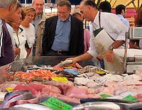 Customer selecting fish at fish stall in outdoor street market, Viale d Papiniano, Milan, Ital