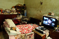Bedridden 90 year old woman watching television. She and her family are under threat of eviction, with insufficent compensation, and threat of physical intimidation, whilst their neighbourhood is already half torn down in preparation for a commercial development.
