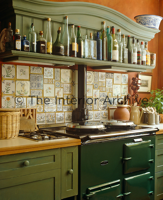 A green Aga has dictated the colour scheme of the kitchen units and the wall has been decorated with a variety of ceramic tiles
