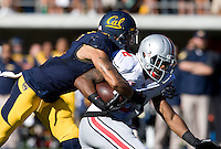 Chris Harper of California tackles Christian Bryant of Ohio State after Bryant intercepted the ball from California quarterback Jared Goff during the game at Memorial Stadium in Berkeley, California on September 14th, 2013.  Ohio State defeated California, 52-34.