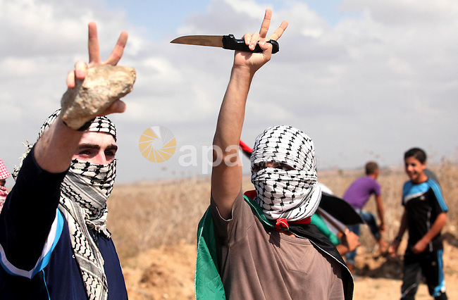 A Palestinian proteser holds a knife during clashes with Israeli security forces near the border fence between Israel and the Gaza Strip on October 9, 2015 east of Gaza City. Tension and protests rose after an Israeli man on 09 October stabbed four Palestinians in southern Israel, in what is being seen as a revenge attack, officials said. On 08 October several violent incidents happened, including stabbings which left eight Israelis injured, one Palestinian was killed in East Jerusalem and six in the Gaza Strip in clashes with the army while at least six were injured on the West Bank . Photo by Ashraf Amra