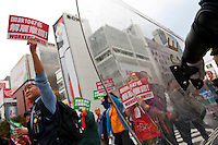 Marxists and Union activists marching in a demonstration are seen through the riot shield of a Japanese policeman at The National Worker`s Rally organised by Marxist groups and Doro Chiba labour union in Tokyo, Japan, Sunday, November 1st 2009