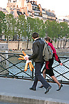 Young couple walking together over the Seine River in Paris, France. Man carrying baguettes/bread.