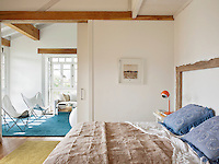 A sliding door set into the partition wall opens the bedroom out into a small living room. The neutral decoration gives the space a light and airy feel.