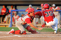 Williamsport Crosscutters catcher Corey Bass (16) tags out Javier Lopez (35) attempting to score a run during a game against the Batavia Muckdogs on August 16, 2013 at Dwyer Stadium in Batavia, New York.  Batavia defeated Williamsport 5-2.  (Mike Janes/Four Seam Images)