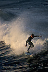 Surfers riding waves at sunrise+Oceanside Beach, Oceanside, San Diego County, CALIFORNIA