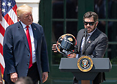 Martin Truex Jr., the NASCAR Cup Series champion, right, presents a racing helmet to United States President Donald J. Trump, left, during an event on the South Lawn of the White House in Washington, DC on Monday, May 21, 2018.  Truex competes full-time in the Monster Energy NASCAR Cup Series for Furniture Row Racing.<br /> Credit: Ron Sachs / CNP