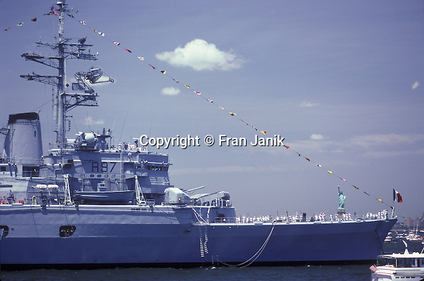 "The French war ship ""Jeanne De Arc""sits at anchor in New York Harbor. The ship is seen during  the celebration for the Statue of Liberty, on July 5th in 1986. The statue frames by the ships flags, is seen in the backround"