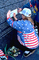 Teen age 13 tracing name on Minnesota Viet Nam Memorial Wall .  St Paul Minnesota USA