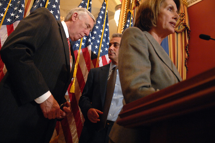 Caucus Chairman Rahm Emanuel, D-Il., center, confers with Majority Leader Steny Hoyer, D-Md., as Speaker Nancy Pelosi, D-Calif., addresses the media during a news conference on SCHIP and other issues.
