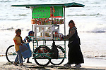 MEXICAN WOMAN AND HER TWO CHILDREN SELL SNACKS ON PUSH CART