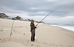Tim Firrman of Brick, NJ fishes for Striped Bass on the beach in Mantoloking, New Jersey.  In the background work by the Army Corp of Engineers on dune construction on the beach in Mantoloking to protect homes continues. (Bill Denver For New York Daily News)
