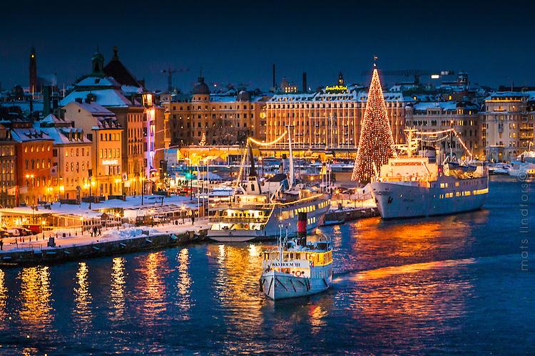 Julgran och julpyntade båtar vid Skeppsbron i Gamla stan Stockholm