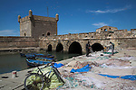 Men working on fishing nets laid out on quayside Port Skala and fortified bridge, Essaouira, Morocco