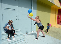 Tonia Hanson (center), owner of Tonia Hanson Photography in Fayetteville, holds balloons Thursday, May 21, 2020, while client Ally Smolinski of Rogers holds her son, Roman Smolinski, 3, taking family photographs with Roman's twin sister Charleston in front of the Maude Wall at Maude Boutique in Fayetteville. The clothing store invites patrons to use their multicolored back wall for photographs. Visit nwaonline.com/200522Daily/ for today's photo gallery.<br /> (NWA Democrat-Gazette/Andy Shupe)