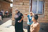 Parashiva Lakatar, 68 Jahre mit Ihrem Enkel Remus (r)) hinter ihrem Haus in Rusciori. Hinten links Ihr Mann. Europa, Rumaenien, Rusciori den 25. Juli 2015