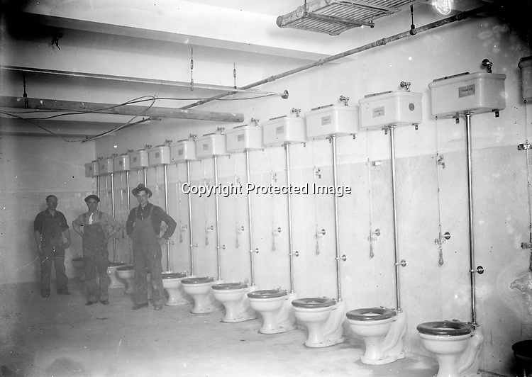 MAIL CARRIERS' TOILET ROOM. The building plans of 1914 for the expansion to Lincoln's courthouse and post office include a &quot;Carriers Swing Room&quot; in the basement adjacent to the &quot;Carriers Toilet.&quot; The latter room was planned and built with 14 toilets arranged along one wall, as well as marble wainscoting. The lack of privacy was quite deliberate--both of the carriers' rooms and many parts of the post office included a &quot;lookout&quot; for covert surveillance by postal inspectors, intended to prevent theft from the mail. John Johnson worked as a janitor in the federal building. This image might be one that only a janitor/photographer would have taken.<br /> <br /> Photographs taken on black and white glass negatives by African American photographer(s) John Johnson and Earl McWilliams from 1910 to 1925 in Lincoln, Nebraska. Douglas Keister has 280 5x7 glass negatives taken by these photographers. Larger scans available on request.