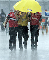 Crew members, who were preparing for Winston Cup qualifying, run for shelter during a passing thunder storm at Chicagoland Speedway. (Photo by Robert Sumner)