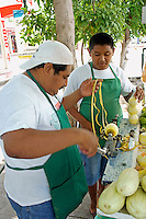 Boy watching his father using a fruit peeling machine at their fruit stand on Avenida Tulum in downtown, Cancun, Quintana Roo, Mexico.