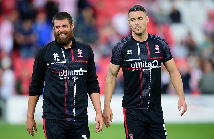 Lincoln City's Michael Bostwick, left and Jason Shackell<br /> <br /> Photographer Andrew Vaughan/CameraSport<br /> <br /> The EFL Sky Bet League One - Lincoln City v Fleetwood Town - Saturday 31st August 2019 - Sincil Bank - Lincoln<br /> <br /> World Copyright © 2019 CameraSport. All rights reserved. 43 Linden Ave. Countesthorpe. Leicester. England. LE8 5PG - Tel: +44 (0) 116 277 4147 - admin@camerasport.com - www.camerasport.com