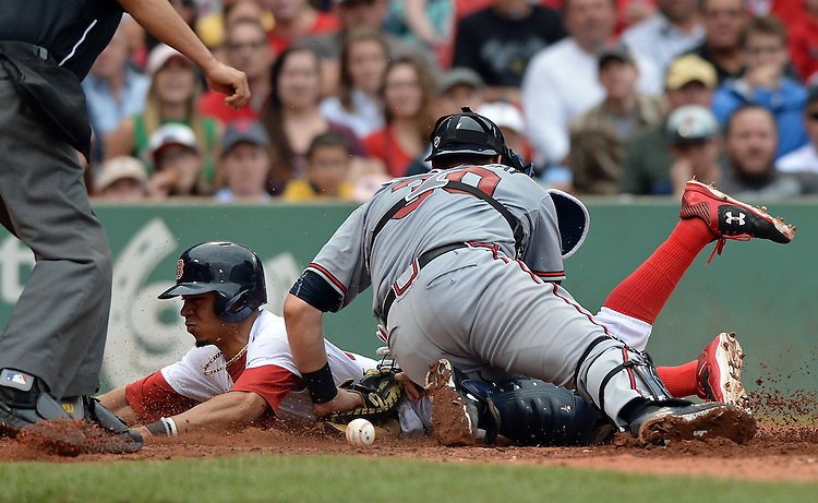 Atlanta Braves catcher Ryan Lavarnway cannot handle the throw as Boston Red Sox's Mookie Betts slides head first into home to score on a single by Xander Bogaerts in the sixth inning of a baseball game at Fenway Park Tuesday, June 16, 2015, in Boston. Photo by Christopher Evans
