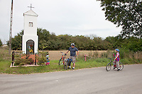Polish bicycling family taking a moment to observe a wayside religious shrine. Zawady Central Poland