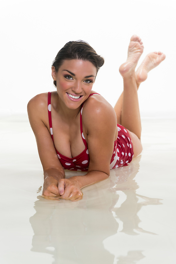 Young caucasian woman in swimsuit with water reflections.
