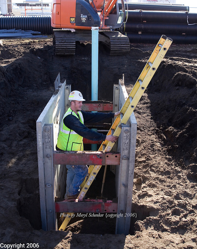 "Pipe layer Jon Daniels installs underground sewer pipe for Looker & Associates, Inc. Daniels is working within the protective confines of a ""trench box,"" a huge steel box that prevents the dirt walls of an excavated trench from collapsing and burying workers in soil."