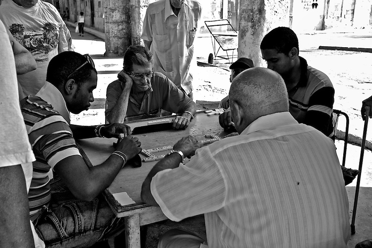 Images from the old Havana, Cuba. ..A pretty common site in Old Havana, people gather - one could say spontaneously -, to play domino.  Many passer-by stand and watch for long periods of time as the game evolves.  They take it very seriously, and there is certainly a lot more strategy and technique at the game of domino than I ever knew.  ..This, like many other activities that happen in the street, drive a social dynamic prone to being outside and socializing, something that it's seen manifested all along the town streets.