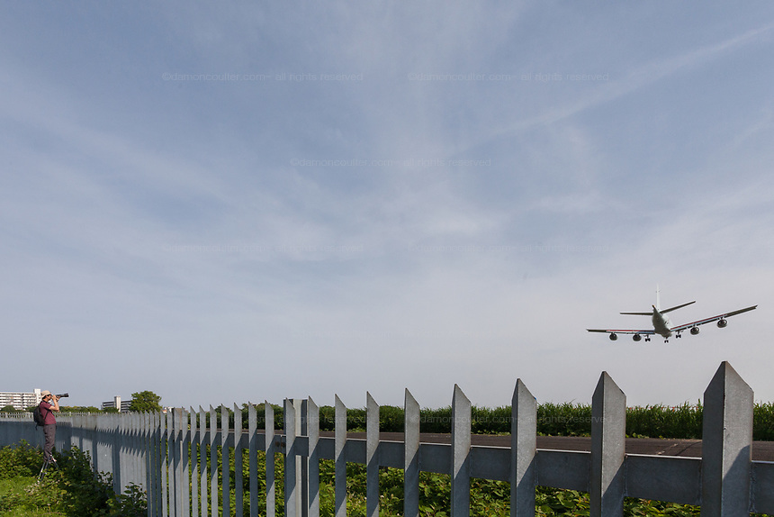 A man with a camera looks over a fence near Atsugi Airbase and watches the military aircraft landing. Yamato, Kanagawa, Japan. Tuesday May 1st 2018